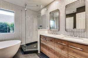 A beautiful bathroom with an enclosed shower, freestanding tub, and cabinet with waterfall countertop is shown