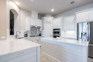 A newly renovated kitchen with bright white cabinetry.