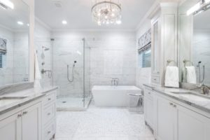 A bright white bathroom with white cabinetry, an enclosed shower, and freestanding tub