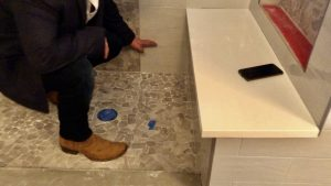 A contractor inspects a shower basin